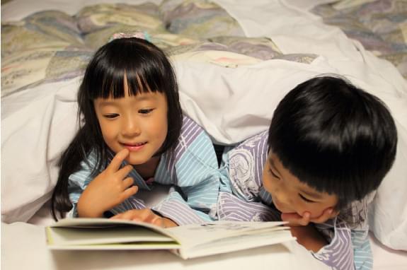 お部屋で絵本を読む子どもたちの写真