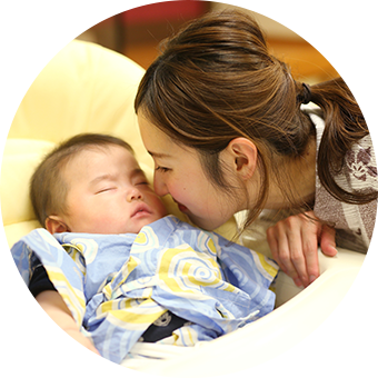 赤ちゃんにキスをするおかあさんの写真